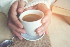 松弛片刻、葡萄酒口气的咖啡和一本书在木桌上在自然背景中,颜色和软的焦点 库存图片