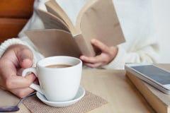 松弛片刻、葡萄酒口气的咖啡和一本书在木桌上在自然背景中,颜色和软的焦点 免版税库存图片