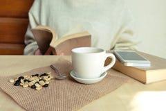 松弛片刻、葡萄酒口气的咖啡和一本书在木桌上在自然背景中,颜色和软的焦点 免版税库存照片