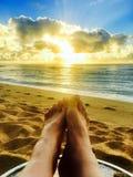松弛的完善的天堂脚观看在海滩的光彩的金黄日出在考艾岛夏威夷 库存图片