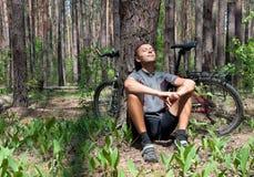松弛自行车骑士在具球果森林里春天 免版税库存照片