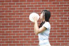 轻松的亚洲中国女孩爆炸气球和享受在草坪的业余时间 免版税图库摄影