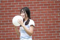 轻松的亚洲中国女孩爆炸气球和享受在草坪的业余时间 免版税库存图片