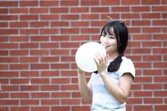 轻松的亚洲中国女孩爆炸气球和享受在草坪的业余时间 库存照片