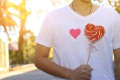 年轻轻松的人拿着女朋友的一个红色心脏糖果有对被弄脏的背景的阳光作用的 拉丁文的约会概念o 免版税库存图片