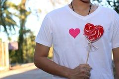 年轻轻松的人拿着女朋友的一个红色心脏糖果被弄脏的背景的 拉丁文的约会概念或华伦泰` s天 库存图片