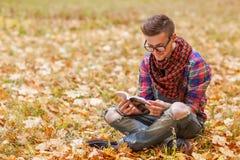 年轻轻松的人阅读书本质上,后面在树,草甸b 库存照片