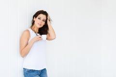 轻松的在白色墙壁上的妇女饮用的咖啡 免版税图库摄影