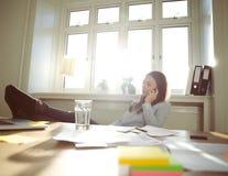 轻松的女实业家在家谈话在手机办公室 免版税库存图片