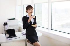 轻松的女实业家饮用的咖啡 免版税库存图片
