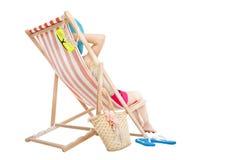 轻松的妇女坐海滩睡椅 库存图片