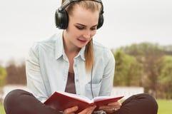 年轻轻松的妇女读书和听的音乐特写镜头  免版税图库摄影