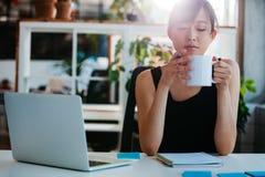轻松的少妇喝咖啡在她的书桌 免版税库存照片