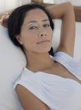 轻松的少妇在床上 免版税库存照片