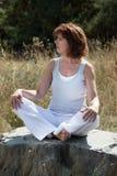 轻松的成熟瑜伽妇女坐石外部 库存图片