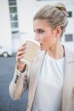 轻松的时髦的女实业家饮用的咖啡 免版税库存照片
