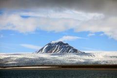 松的白色云彩、蓝天、山峰和冰川在北极斯瓦尔巴特群岛 库存照片