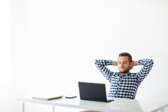 轻松的英俊的人与膝上型计算机坐白色背景 免版税库存图片