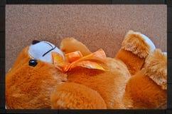 轻松的谎言熊玩偶有棕色背景 免版税库存图片