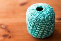 绿松石在木头的棉纱品球  库存照片