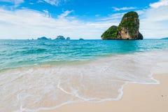 绿松石干净的海和白色泡沫在含沙岸 库存图片