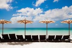 绿松石海、deckchairs、白色沙子和沙滩伞 免版税库存图片