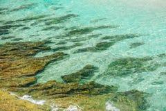绿松石海洋和金黄颜色看法向背景扔石头 库存图片