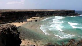 绿松石的两位孤独的冲浪者浇灌偏僻的海滩海浪斑点 股票视频