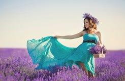 绿松石礼服的孕妇在淡紫色领域 免版税库存照片