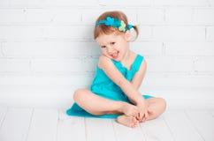 绿松石礼服的美丽的矮小的女婴 免版税图库摄影