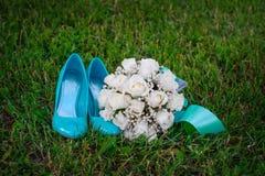 绿松石穿上鞋子新娘和白色婚礼花束在草 图库摄影