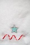 绿松石蓝星和在雪的红色打旋的丝带 免版税库存图片