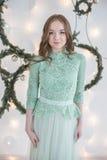绿松石装饰的白色墙壁的晚礼服的妇女 库存图片