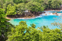绿松石,与一个白色房子的天蓝色的海湾岩石的 免版税库存图片