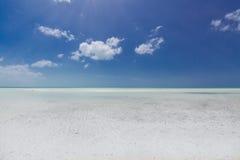 绿松石,合并与清楚的美丽的天空的平静的海洋在天际线在晴朗的温暖的天 免版税库存图片