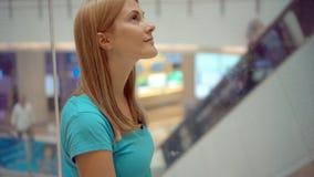 绿松石T恤杉骑马的愉快的微笑的少妇在查寻购物中心的电梯 股票视频