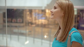 绿松石T恤杉骑马的愉快的微笑的少妇在查寻购物中心的电梯 股票录像