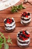 松糕一个甜点心与奶油的在一块玻璃用在木黑暗的背景的新鲜的莓果 库存图片