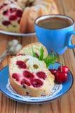 松糕用在蓝色板材的樱桃 免版税库存照片