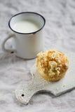 松饼和杯子轻的表面上的牛奶 免版税库存图片