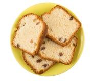 松饼片断用在黄色茶碟的葡萄干在白色 免版税库存图片