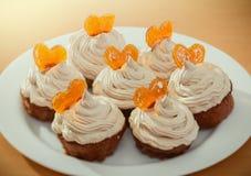 松饼,与奶油色和焦糖的心脏的杯形蛋糕 图库摄影