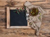 黑板、碗筷和橄榄顶视图与橄榄油 免版税库存图片
