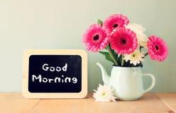 黑板与对此写的词组早晨好在有鲜花的花瓶旁边 库存照片