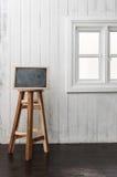 黑板和圆的木椅子在一个黑暗的木材木地板上, n 免版税库存照片