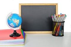 黑板和学校用品在桌上 库存照片