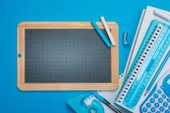 黑板和文具在蓝色背景 免版税库存图片