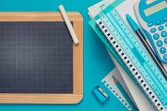 黑板和文具在蓝色背景 免版税图库摄影