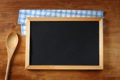 黑板和木匙子顶视图在木桌 免版税图库摄影