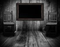 黑板和木头椅子在有灰色木墙壁的内部屋子里 库存图片